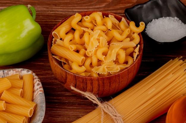 Вид сбоку различных макарон в миске и в тарелке с солью перца на деревянный стол