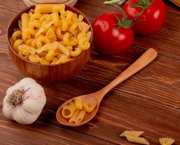 Вид сбоку различных макарон в деревянной миске и ложке с чесноком и помидорами на деревянном столе
