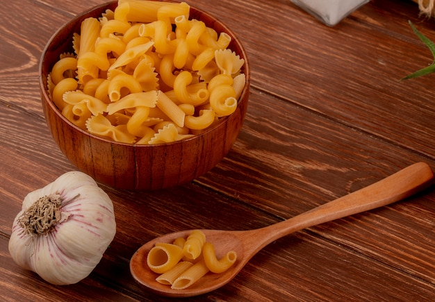 Вид сбоку различных макарон в деревянной миске и ложке с чесноком на деревянном столе