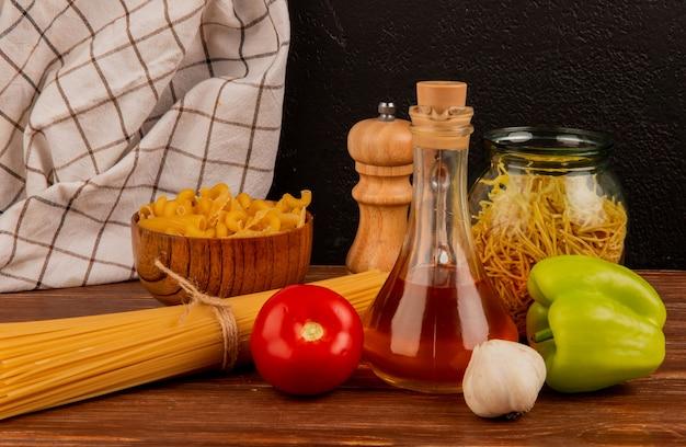 Взгляд со стороны различных макарон с солью перца томата чеснока топленого масла и тканью шотландки на деревянной поверхности и черной поверхности