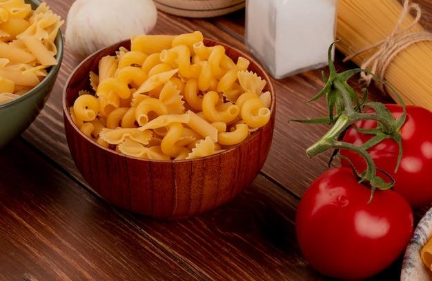 Взгляд со стороны разных видов макарон в шарах и томатном чесноке соли на деревянном столе