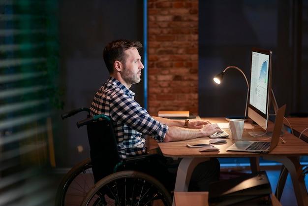 Вид сбоку бизнесмена-инвалида, работающего в офисе