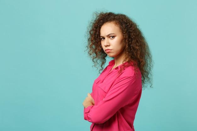 파란색 청록색 배경에 격리된 채 손을 잡고 카메라를 바라보는 분홍색 캐주얼 옷을 입은 당황한 아프리카 소녀의 측면. 사람들은 진심 어린 감정 라이프 스타일 개념입니다. 복사 공간을 비웃습니다.