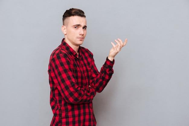Вид сбоку недовольного молодого человека в рубашке, делая недовольный жест. изолированный серый фон