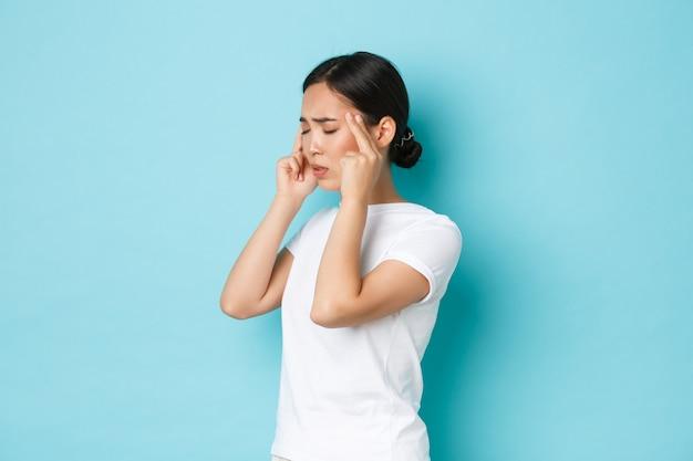 Вид сбоку на головокружение, стресс или истощение молодой азиатской женщины, которая плохо себя чувствует, закрывает глаза и массирует виски, у нее головная боль, жалуется на мигрень, стоит синяя стена