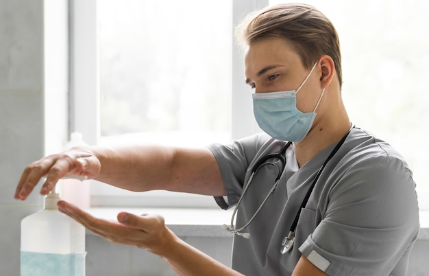 Вид сбоку на врача с медицинской маской, использующего дезинфицирующее средство для рук