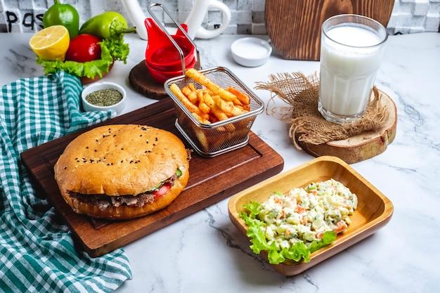 Вид сбоку донер-кебаб с мясом в лаваше на деревянной доске с овощным салатом, картофелем фри и айранским напитком