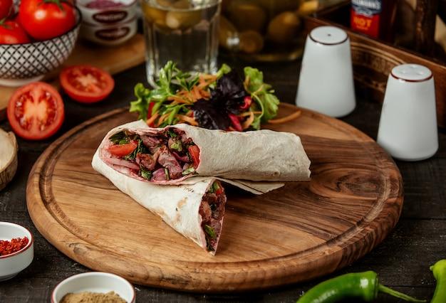 Вид сбоку донер кебаб, завернутый в лаваш со свежим салатом на деревянной доске