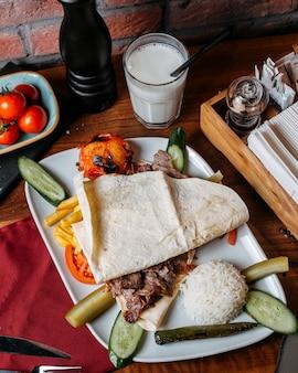 Вид сбоку донер мясо с картофелем фри рисом и овощами на тарелке