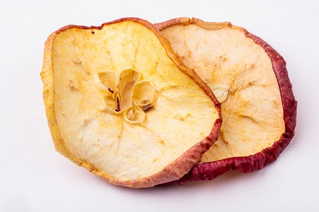 Вид сбоку сушеных яблочных ломтиков на белом фоне
