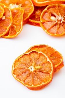 Вид сбоку сушеные апельсиновые дольки расположены на белом фоне
