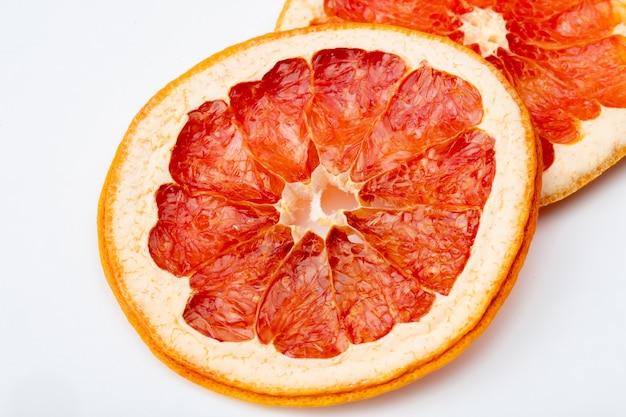 Вид сбоку сушеные апельсиновые дольки на белом фоне