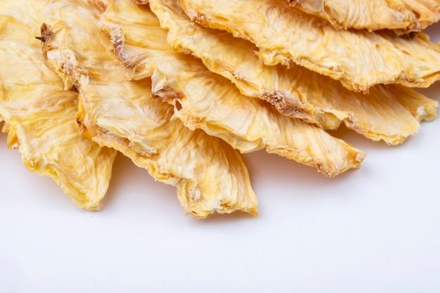 Вид сбоку сушеных ломтиков ананаса, изолированных на белом фоне
