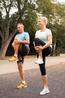 屋外で運動する前にウォーミングアップする老夫婦の側面図