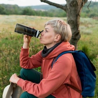 高齢者の観光客の女性が水を飲むの側面図