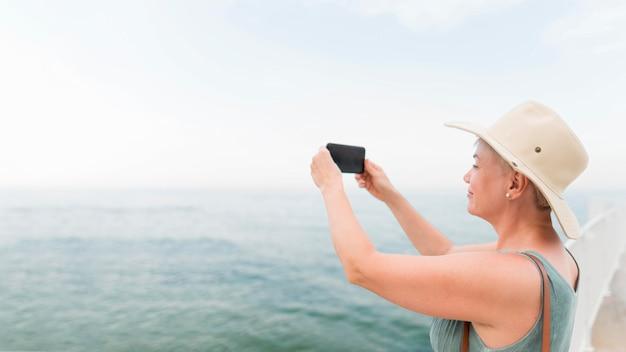 海で写真を撮る高齢者の観光女性の側面図