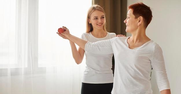 아령으로 운동을하는 covid 회복 노인 여성의 측면보기