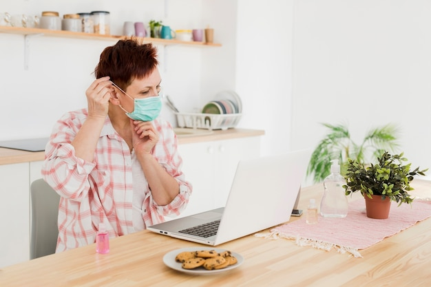 Вид сбоку пожилой женщины, надевая медицинскую маску дома, прежде чем работать на ноутбуке