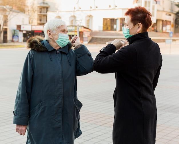 お互いに敬礼する肘に触れる医療用マスクを持つ高齢者の女性の側面図