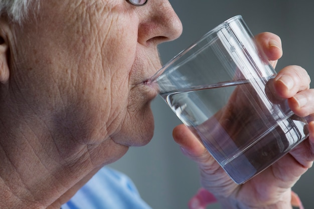물을 마시는 노인 여성의 측면 보기