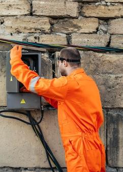 Электрик в униформе и защитной маске, вид сбоку