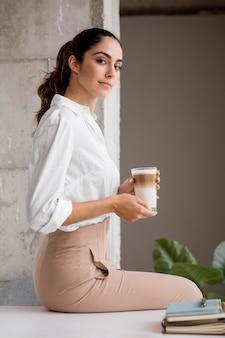 Элегантная деловая женщина позирует с кофе, вид сбоку