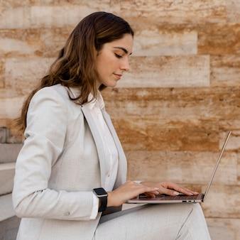 屋外のラップトップで動作するスマートウォッチとエレガントな実業家の側面図