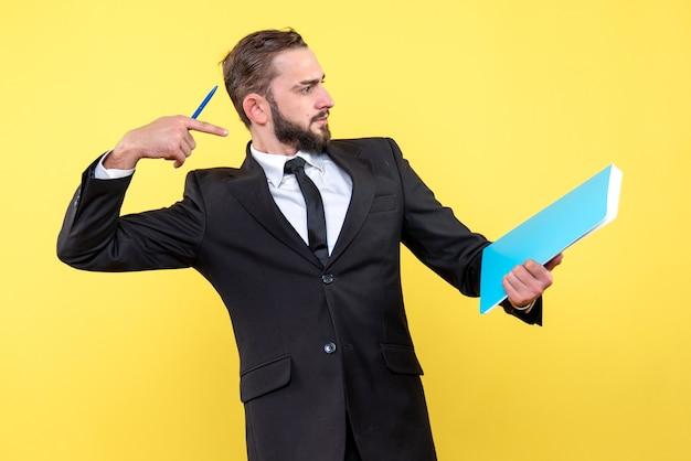 黄色の壁の青いフォルダーに指を指している感情的なビジネスマンの側面図