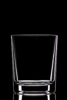 Вид сбоку пустой стеклянной чашки на темной стене со свободным пространством