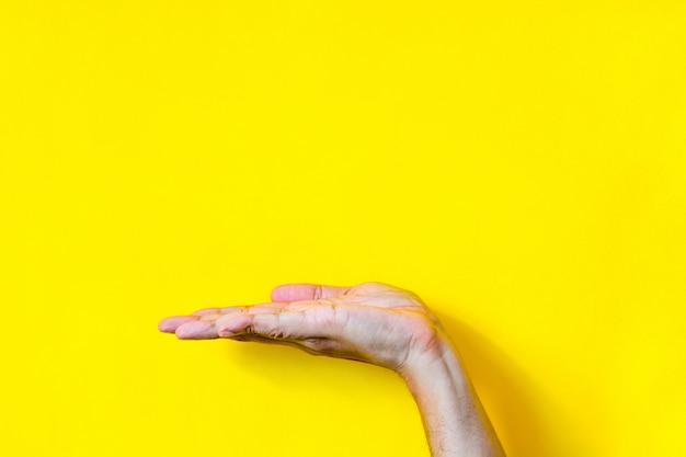 Вид сбоку пустой открытый ладони жест рукой мужской руки на желтом фоне