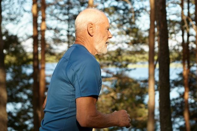 白髪、あごひげ、筋肉質の体を持った元気でアクティブな年配の男性の側面図。川岸沿いの森を高速で走り、健康的なライフスタイルと新鮮な朝の空気を楽しんでいます。アクションショット