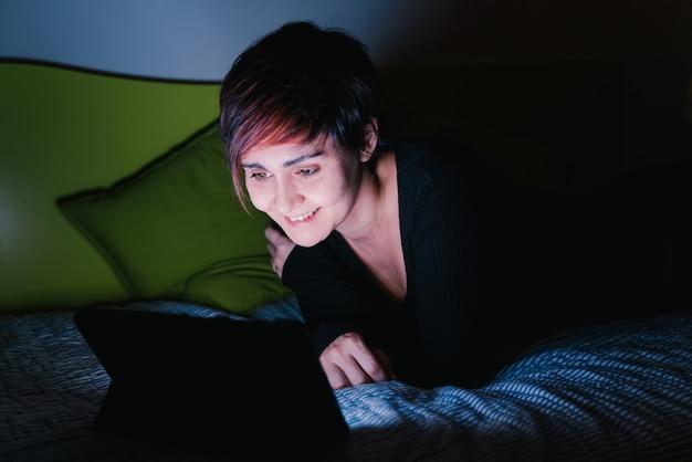 밤에 태블릿 장치와 친구를 호출하는 유럽 여자의 모습. 사람들은 새로운 기술 개념에 중독되었습니다. 가정 생활을 유지하십시오.