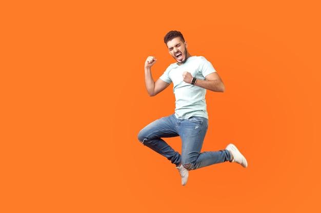 Вид сбоку на чрезвычайно счастливого человека в белом костюме, прыгающего в воздухе с поднятой рукой, жестикулирующего: да, я сделал это, я победитель, громко кричу от радости, чувствуя себя энергичным и живым. изолированные на оранжевом фоне