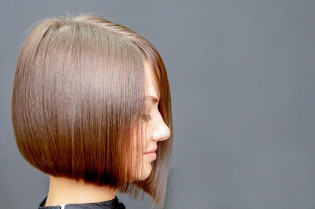 Вид сбоку лица портрет молодой женщины с короткой прической в парикмахерской.