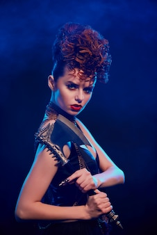 Вид сбоку фантастической девушки с острым топором на синей стене.