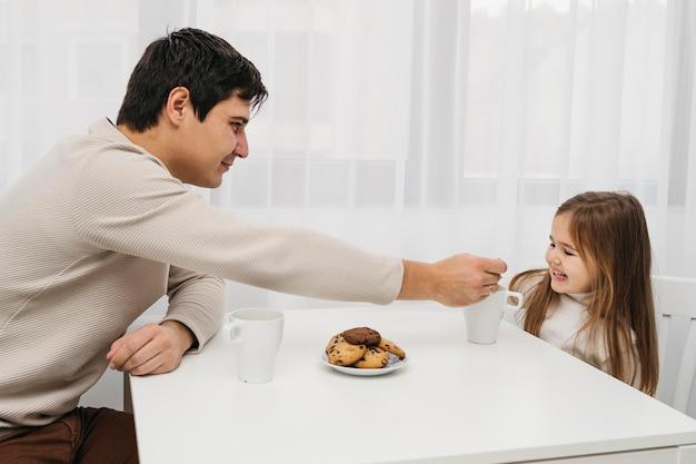 家で一緒に時間を過ごす父と娘の側面図