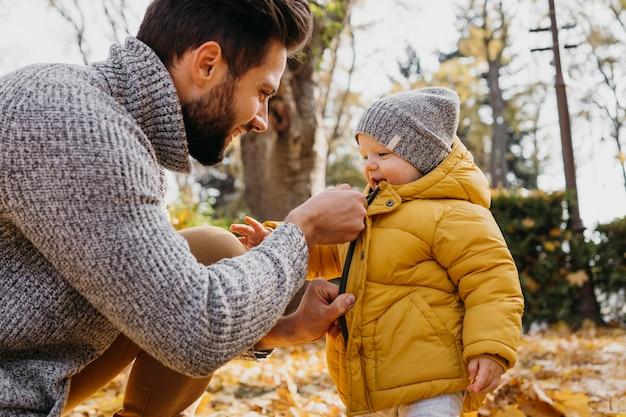 赤ちゃんと一緒に屋外で時間を過ごす父親の側面図