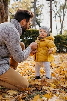 外で赤ちゃんと一緒に時間を過ごす父親の側面図