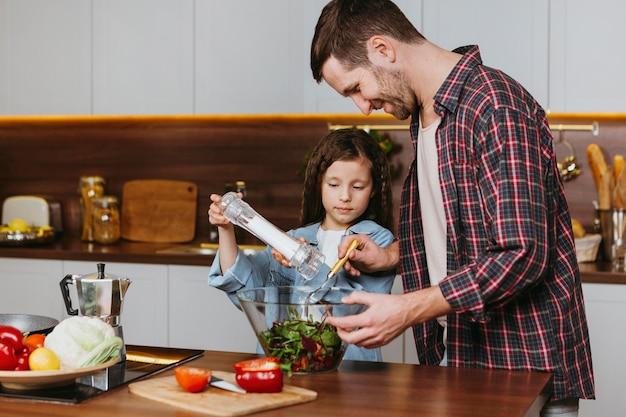 Отец с дочерью, вид сбоку готовит еду на кухне