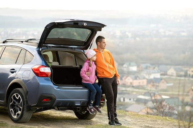 열린 트렁크와 자연을 즐기는 차 근처에 서 있는 어린 딸과 함께 아버지의 측면 보기. 가족과 함께하는 주말의 개념.