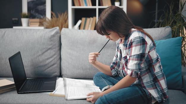 本とラップトップでソファに座って宿題をしている家で勉強している青年期の女性の側面図