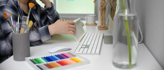 태블릿, 컴퓨터 및 페인팅 도구를 사용하는 여성 아티스트의 측면보기