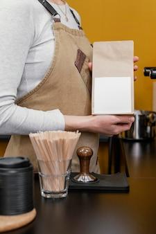 종이 커피 가방을 들고 여성 바리 스타의 측면보기