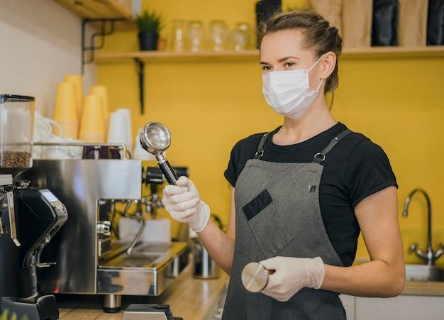 기계 용 커피를 준비하는 의료 마스크와 여성 바리 스타의 측면보기