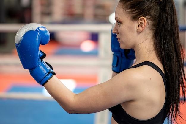 リングの横にある女性のボクサーの側面図