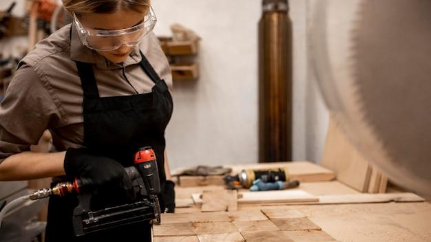 空気圧ホッチキスで女性の大工の側面図