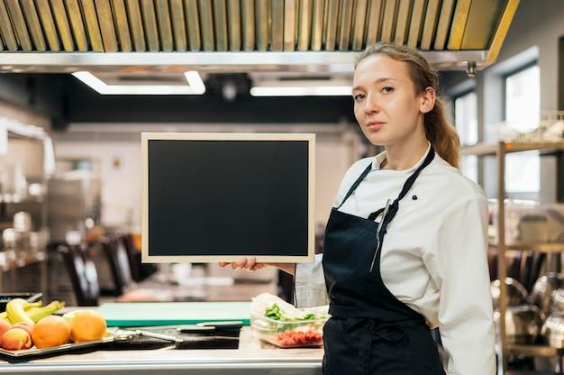 キッチンでポーズをとって女性シェフの側面図