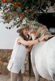 Женщина-фермер, чистящая лошадь на ранчо, вид сбоку