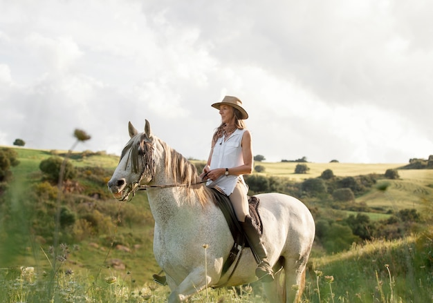自然の中で乗馬する女性農家の側面図
