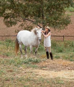 그녀의 말을 쓰다듬는 여성 농부의 측면보기
